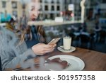 Small photo of Fashion girl using her smartphone for chatting and having chocolate doughnut behind glass of beanery.