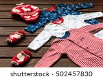 Stock photo baby boy clothes sleepsuits knitted hat and mittens on brown wooden background 502457830