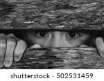 Small photo of a young boy slave imprisoned, retarded, Child Abuse,hand out and eye through wooden sheet, in white tone with shadow edge