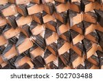 Small photo of Triangle pattern of brown stack roof tiles texture in overlapping layers ready to build and construction for background