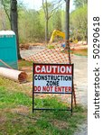 Caution - Construction Zone Sign in Front of Industrial Worksite - stock photo
