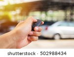 Small photo of Men's hand presses on the remote control car alarm systems with sunlight