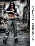 Young strong woman in ruined building. High contrast colors. - stock photo