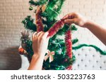Small photo of Hands decorating Christmas tree with red tinsel. Close-up of green pine-tree decorated with sparkling trumpery and bows. Holiday, winter, happiness concept