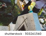 Small photo of Woman cleans a grave with brush. November 1 All Saints' Day