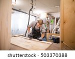 tattoed man polishes boards.... | Shutterstock . vector #503370388