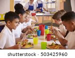 Stock photo primary school kids eating at a table in school cafeteria 503425960