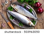 Stock photo salted herring with red onion and parsley on the old wooden background 503963050