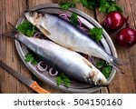 Stock photo salted herring with red onion and parsley on the old wooden background 504150160