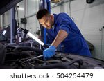 car service, repair, maintenance and people concept - auto mechanic man with lamp working at workshop - stock photo