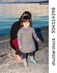 Small photo of KOS, GREECE, CIRCA OCTOBER 2015. Afghan immigrant baby with her mother in the coast of Aegean Sea. They crossed the water from Turkey in a dinghy.