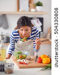 young woman eating fresh salad... | Shutterstock . vector #504330808
