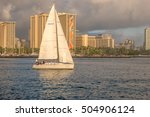 Small photo of Honolulu, Hawaii, USA, Oct. 26, 2016: White racing sailboat leaving the Alia Wai Harbor in light evening winds.