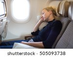 Small photo of Tired blonde casual caucasian lady napping on seat while traveling by airplane. Commercial transportation by planes.