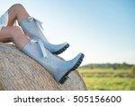 Girl In Rain Boots Sitting On...