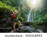 young woman backpacker looking at the waterfall in wild jungles.