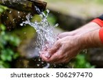 Stock photo washing hands in fresh cold potable source water on a mountain drinking spring wooden pipe of 506297470