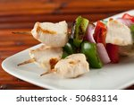 closeup of cubed chicken kabobs with red peppers, green peppers and red onion plate - stock photo