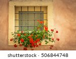 Red Flowers In The Window Of A...