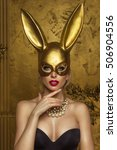 Stock photo beautiful blonde young woman in carnival gold rabbit mask with long ears 506904556