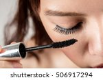 Woman Applying Mascara On...