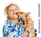 Small photo of happy senior adult woman holding an affectionate chihuahua dog