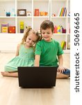 Kids with laptop, sitting on the floor playing - stock photo