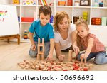 Woman and kids playing with wooden blocks laying on the floor - stock photo