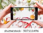 Small photo of Christmas decoration photography on smartphone. Close-up of female hands holding mobile phone with festive trumpery, citrus and xmas tree
