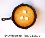 Stock photo butter melting on hot cornbread that was cooked in a black cast iron skillet isolated on white 507216679
