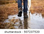 Stock photo man in hiking boots and jeans walking with dog in a rainy day swamp or a farm bad weather 507237520