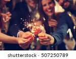 Small photo of Picture showing group of friends having fun with sparklers