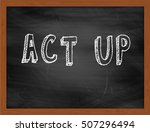 Small photo of ACT UP hand writing chalk text on black chalkboard