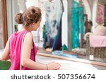 Small photo of Portrait of a beautiful colorful teenager girl looking at clothing store glass window holding shopping bags, smiling outdoors. Adolescent consumer adolescent spending, fashion exterior, lifestyle.