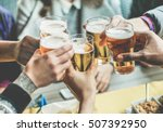 Stock photo multiracial group of friends enjoying a beer young people hands toasting and cheering aperitif 507392950