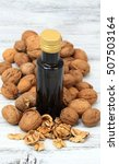 Small photo of Walnut oil from walnut kernels in a brown bottle , walnut shells around it and whole walnuts on the wooden table