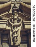 Small photo of Bucharest, Romania - April 22, 2014: Carved bas-relief depicting two serpents twined around the winged caduceus staff as a symbol of commerce, on the frontispiece of the Stock Exchange Palace.