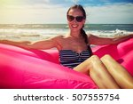 Small photo of A shot of a woman wearing brown sunglasses and a striped swimming suit sitting on the pink airboat on the beach on a sunny day. The skinny female whose brown hair is tying into braid is smiling