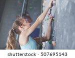 Teen Girl Climbing A Rock Wall...