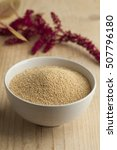 Small photo of Bowl with amaranth seeds and a twig with flowers on the background