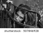 Small photo of Curly young woman aggressively holding staircase ragged lattice. black and white photo
