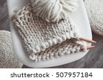 Small photo of Thick yarn and wooden needles on modern plastic chair in living room, top view. Chunky knit.