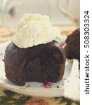 Small photo of Chocolate fondant, souffle cake with whipped cream on decorative plate, toned