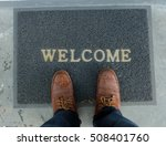 Small photo of Welcome carpet with foot-ware on it