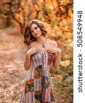 Small photo of Luxurious lady in the bright dress. Nice smile, playful gait. Attire with bare shoulders. Fabulous Golden autumn trail. The picturesque nature.Fantastic shooting. Fashionable toning. Creative color.