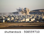 Small photo of Suruc, Turkey - October 21, 2014. Smoke rises in Kobani, Syria, after an airstrike by the U.S.-led coalition, as seen from the top of a hill near Suruc, at the Turkish - Syrian border.