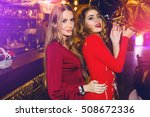 Stock photo fashionable girls best friends posing in restaurant or night club in stylish sensual red dress 508672336