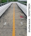 Small photo of white arrow icon and straight lines bisect yellow color, The pathway on the pedestrian overpass