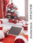 Small photo of Santa Claus waiting for Christmas and connecting with a digital touch screen tablet with decorations and gifts all around