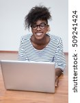 Small photo of Happy African American woman with a lovely frizzy afro hairdo lying on the wooden floor with a laptop computer smiling at the camera with a blank white wall and copyspace behind her